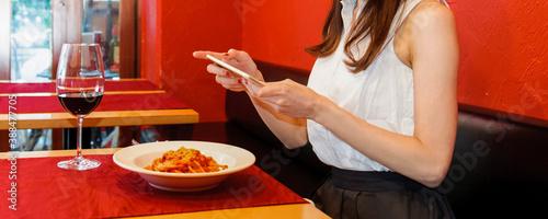 レストランで、スマホで料理の写真を撮影する若い女性 Fotobehang