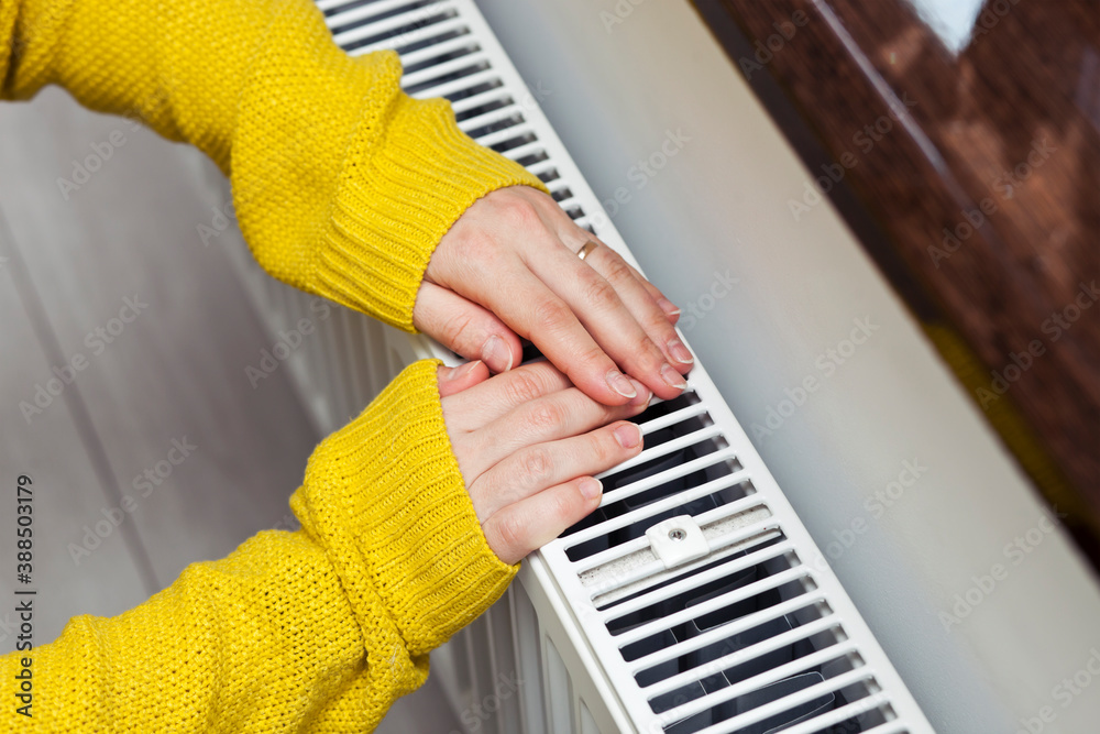 Fototapeta The woman warms her hands on the radiator