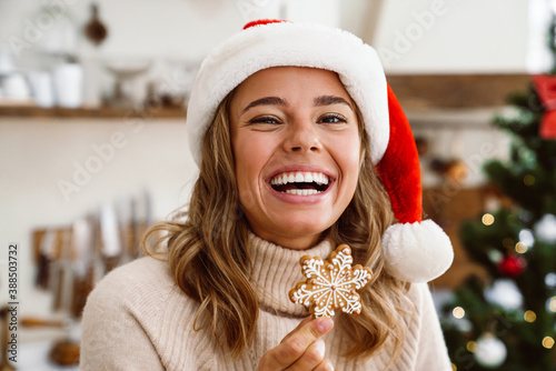 Happy cute woman in santa claus hat laughing and eating Christmas cookie Fotobehang