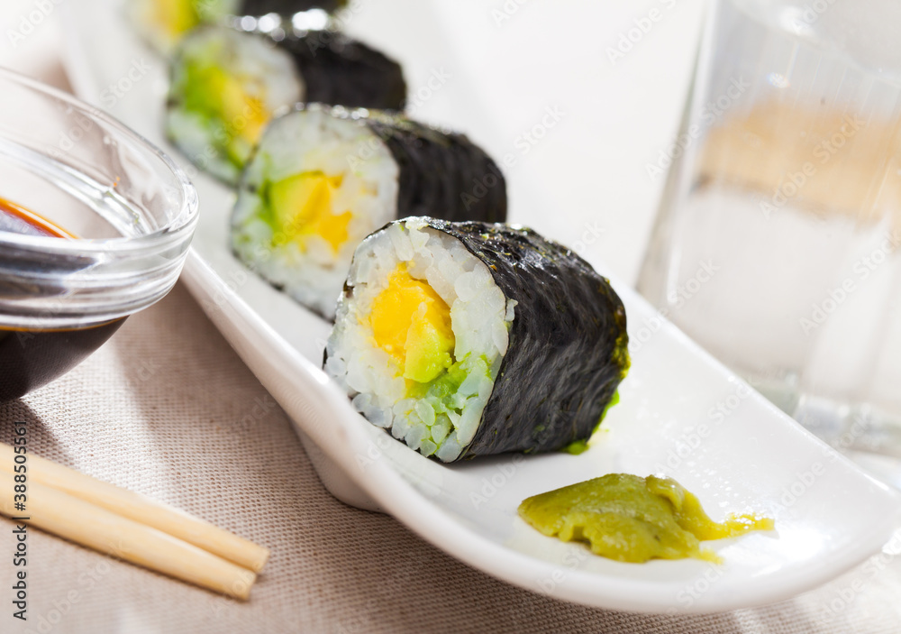 Obraz Tasty Maki roll with avocado served on plate with sauce fototapeta, plakat