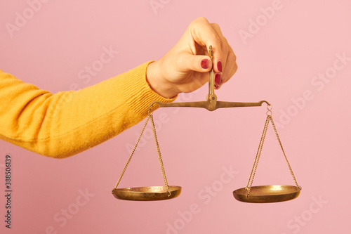 woman hand holding a balance on pink background Fototapeta
