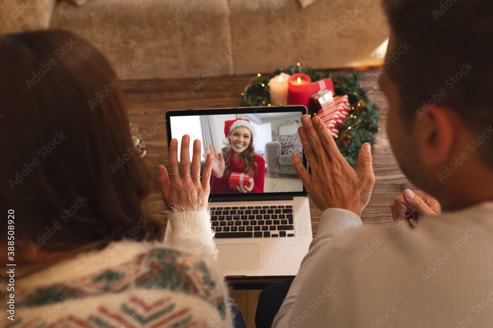 Fototapeta Rear view of couple waving while having a videocall with woman in santa hat waving while holding gif