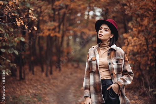 Obraz Beautiful woman enjoing autumn day. Beauty and fashion. Autumn fashion and lifestyle. Pretty woman wearing warm autumn clothes, hat and yellow scarf. Autumn mood. Fashionable woman outdoors. - fototapety do salonu