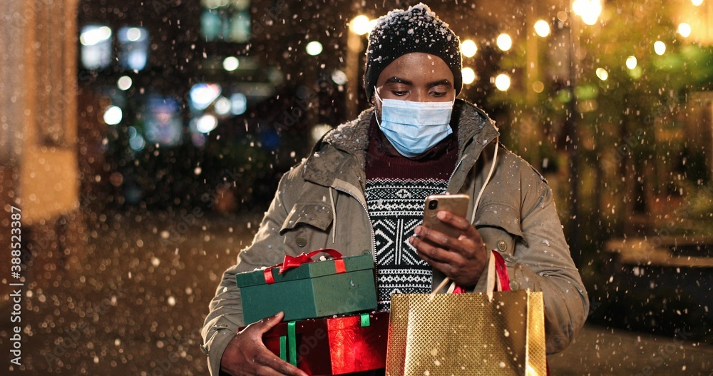 Fototapeta Portrait of man standing and texting on mobile phone. Young African American happy male with little Christmas tree and shopping bags typing on smartphone while snowing. Winter holidays concept