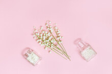 Small Flowers Of Lilies Of The Valley And Glass Bottle With Dry Petals On Soft Pink Background With Copy Space For Text. Spring Time And Aromatherapy. Spa Flat Lay.