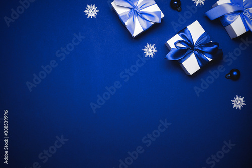 Obraz Winter background blue. White gift with cyan bow, blue balls and winter tree in xmas decoration on azure background for greeting card. Winter festive composition with copy space. - fototapety do salonu