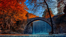 Old Arched Bridge In Front Of A Waterfall In Autumn