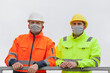 Leinwandbild Motiv Two workers or engineers with face mask standing on a construction site or  an industrial railing