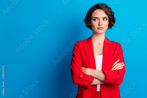 Portrait of attractive brown-haired lady folded arms looking aside copy space isolated over bright blue color background