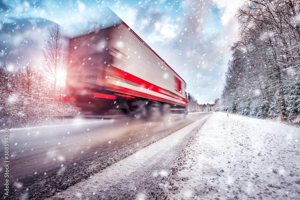 Fototapeta Truck on asphalt road in winter on sunny morning