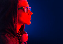 Portrait Of A Woman Dressed In Hooded, Sunglasses And Headphones.