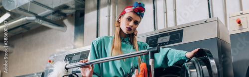 Cuadros en Lienzo young and stylish woman in turban standing near washing machines in modern laund