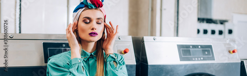 Valokuvatapetti trendy woman with closed eyes touching turban in modern laundromat, banner