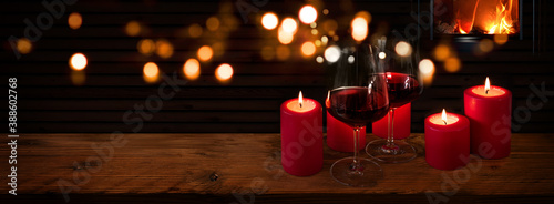 Fotografie, Obraz Glasses of red wine with candles on rustic wood in front of a log fire and golden bokeh lights