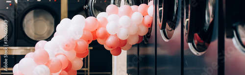 Fotografiet pink balloons near modern washing machines in laundromat, banner