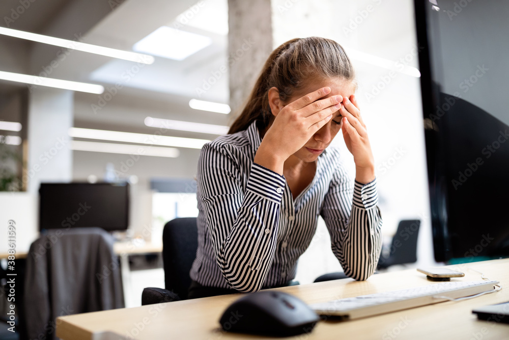 Fototapeta Overworked and frustrated young woman in front of computer in office