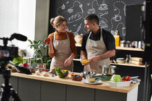 Happy Young Couple In Aprons S...