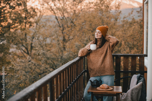 Fotografie, Obraz Young woman in knitted sweater and hat drinking tea and eating fresh croissants on cozy balcony of a wooden country house