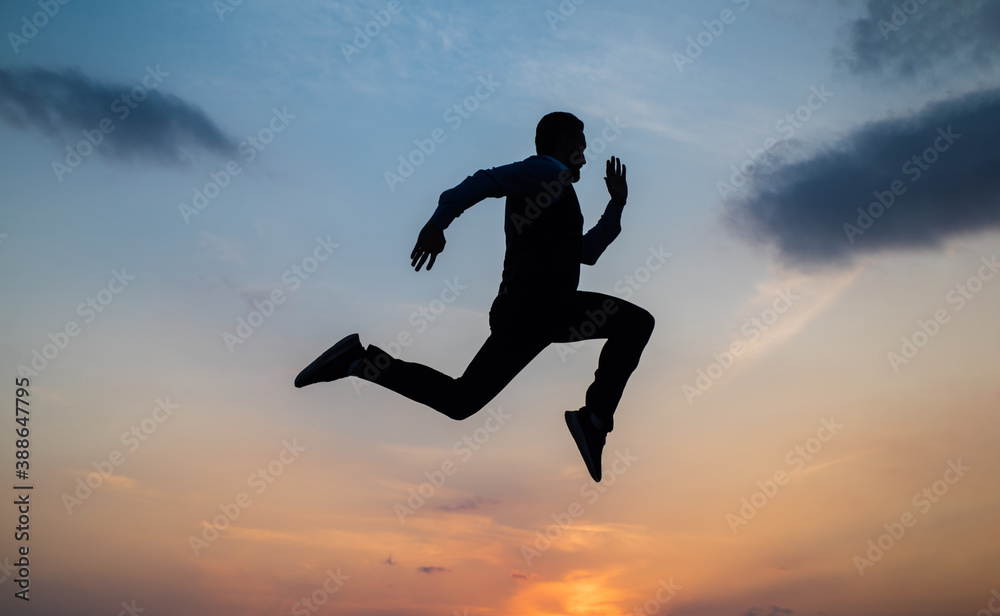 Fototapeta Find your freedom. personal achievement goal. man silhouette jump on sky background. confident businessman running. daily motivation. enjoying life and nature. business success. freedom