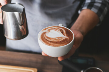 Barista making hot coffee in cafe, closeup