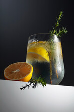 Alcohol Drink (gin Tonic Cocktail) With Lemon, Juniper Branch, And Ice On A Dark Background.