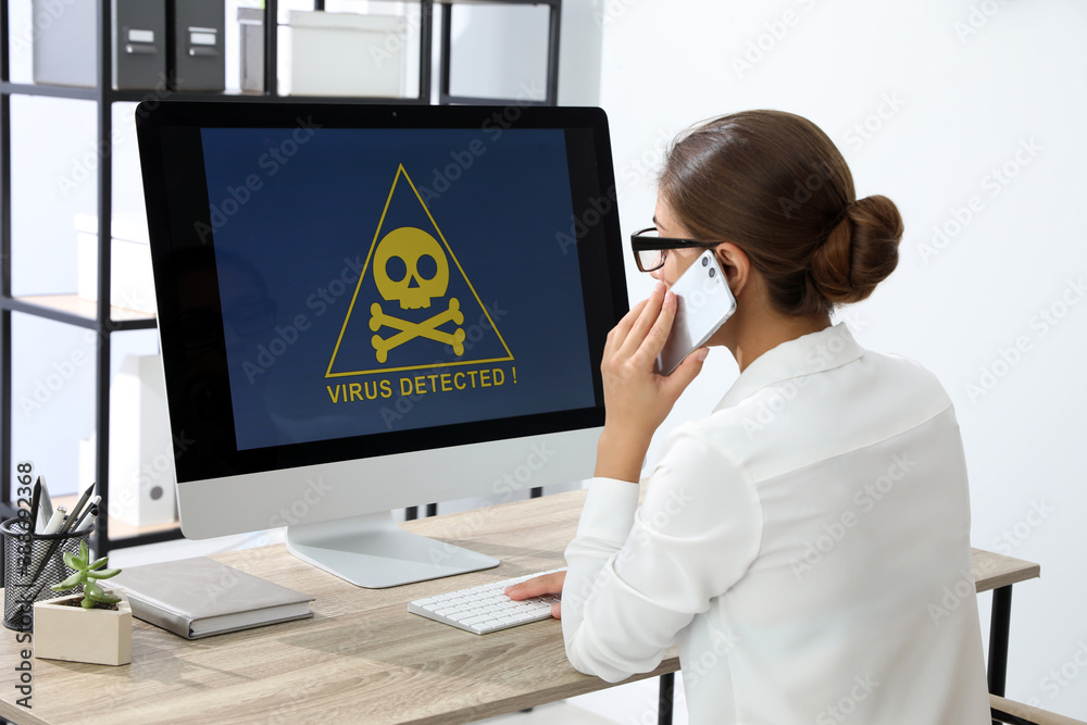 Fototapeta Office worker in front of computer with warning about virus attack on screen