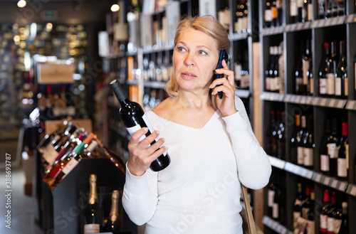 Obraz na plátně Modern stylish mature woman talking on phone advising with someone about purchasing of wine in winehouse