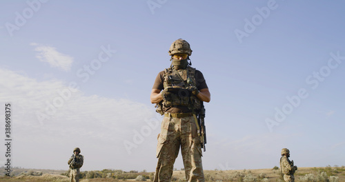 Soldiers protecting commander while surveilling enemy territory Fototapeta