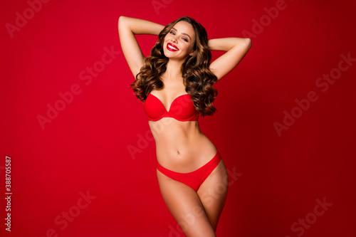 Obraz Photo of attractive seduce beauty curly lady advertising underwear novelty sensual slim fit body bright pomade arms behind head wear brassiere panties isolated red color background - fototapety do salonu