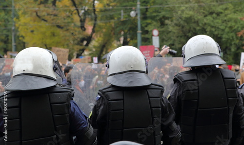 Fotografiet Three policemen in full uniforms with white helmets stand opposite of of protest