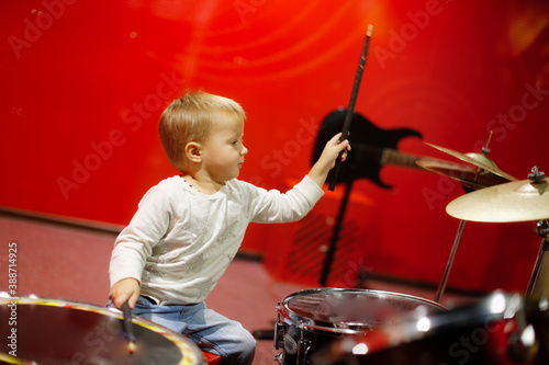 Toddler kid playing drums on red background, kid playing drum kit, concept music Canvas