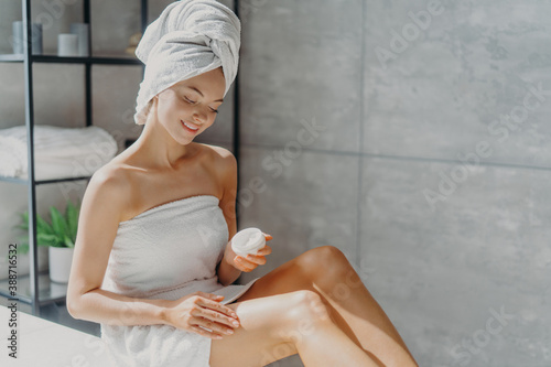 Fotografie, Obraz Photo of sensual young European woman uses body cream after taking bath takes care of her skin wrapped in white towel poses against bathroom background