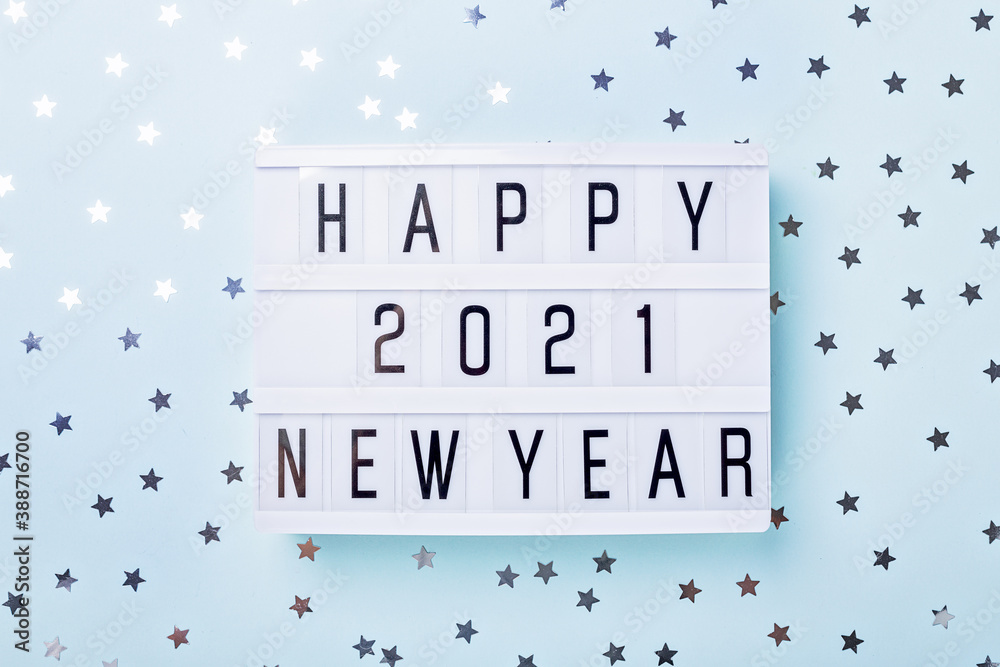 Fototapeta Lightbox with text HAPPY NEW YEAR 2021 on blue background. Top view. New year celebration. Happy New Year 2021 concepts