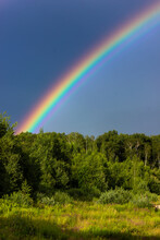 Rainbow Over The Summer Mixed Forest, Cloudy Sky And Clear Rainbow Colors, Forest Road. Natural Landscape. Rainbow Colors After Rain. Rain Clouds.