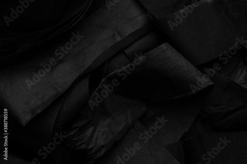 Fototapeta Discarded wrinkled black stripes of textured synthetic material with protruding threads obraz na płótnie