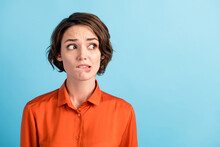 Closeup Photo Of Sad Depressed Displeased Lady Horrified Facial Expression Made Huge Big Mistake Feel Guilty Look Side Empty Space Bite Lips Wear Orange Shirt Isolated Blue Color Background