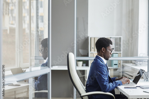 Obraz African businessman sitting at his workplace typing on laptop he working online at office - fototapety do salonu