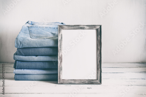 Blank photo frame mockup and stack of blue jeans on an old white wooden table Canvas Print
