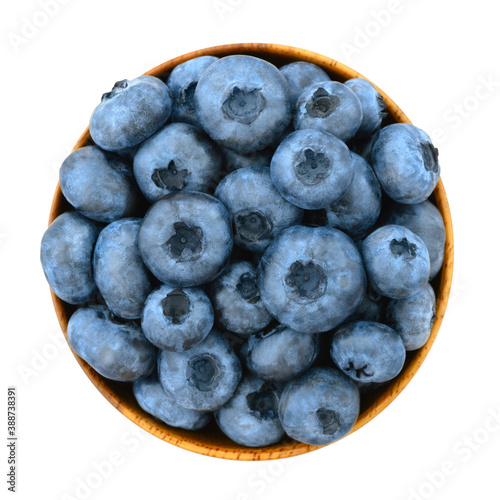 Vászonkép The blueberries in the wooden bowl is isolated on the white background, the top view