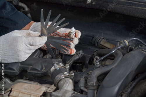 A man with gloves checks the spark plug gap with a feeler gauge Fotobehang