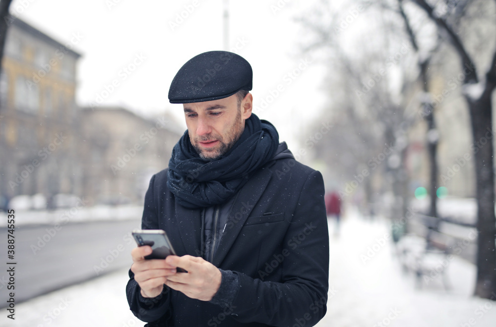 Fototapeta young man writes with smartphone walking in a snowy street