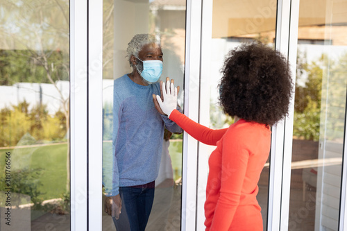 Senior man wearing face mask touching each other through window glass
