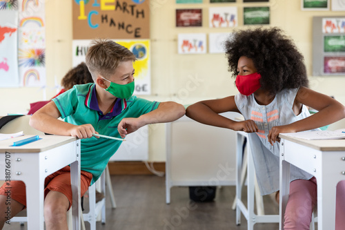 Obraz Boy and Girl wearing face masks greeting each other by touching elbows at school - fototapety do salonu