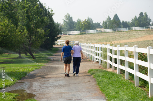 Senior woman walks with companion down a path in a park lined with trees and wat Canvas