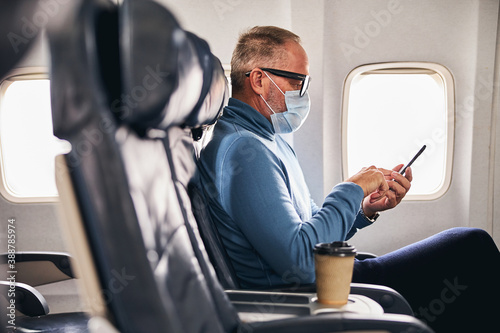 Papel de parede Man with a gadget sitting in the aircraft cabin