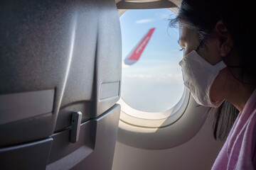 A traveler was in a plane on a tour during the Covid-19 epidemic, wearing a face mask, looking outside from the plane's window