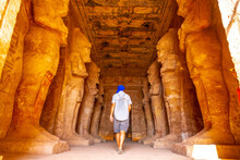 A Young Tourist In A Blue Turban Looking At The Pharaohs At The Abu Simbel Temple In Southern Egypt In Nubia Next To Lake Nasser. Temple Of Pharaoh Ramses II, Travel Lifestyle