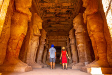 A Couple At The Abu Simbel Temple Next To The Sculptures, In Southern Egypt In Nubia Next To Lake Nasser. Temple Of Pharaoh Ramses II, Travel Lifestyle