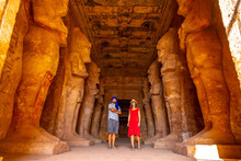 A Tourist Couple At The Abu Simbel Temple Next To The Sculptures, In Southern Egypt In Nubia Next To Lake Nasser. Temple Of Pharaoh Ramses II, Travel Lifestyle