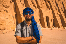 A Young Man Wearing A Blue Turban Visiting The Egyptian Temple Of Nefertari Near Abu Simbel In Southern Egypt In Nubia Next To Lake Nasser. Temple Of Pharaoh Ramses II, Travel Lifestyle